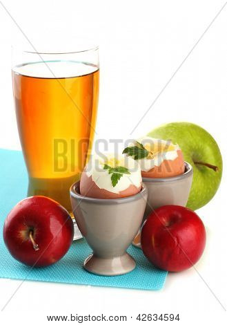 Light breakfast with boiled eggs and glass of juice, isolated on white