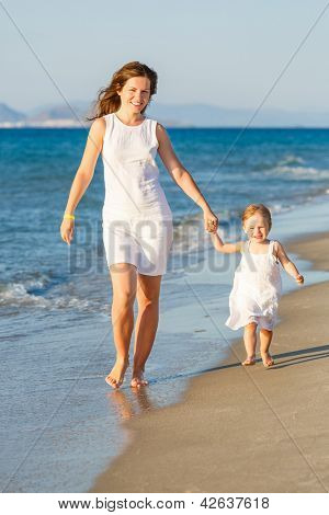 Mother and little daughter walking on the beach