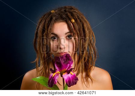Beautiful Young Woman With Dreadlocks Against A Dark Background