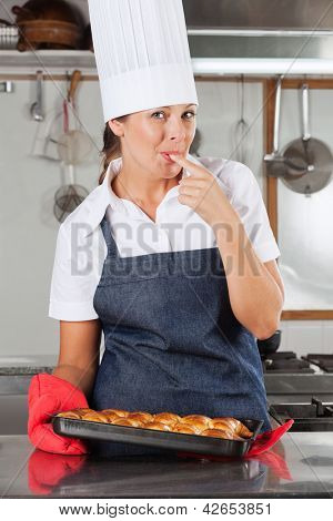 Portrait of happy female chef licking finger while holding bread tray in kitchen
