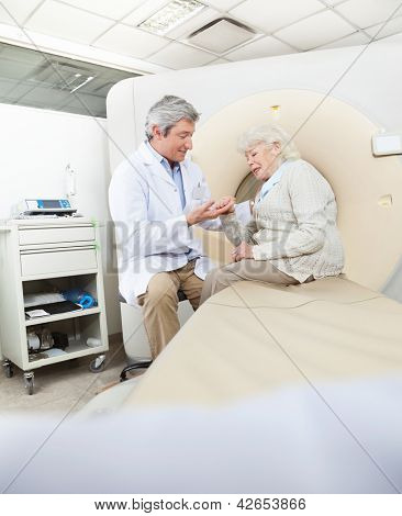 Mature male radiologist comforting senior female patient before CT scan