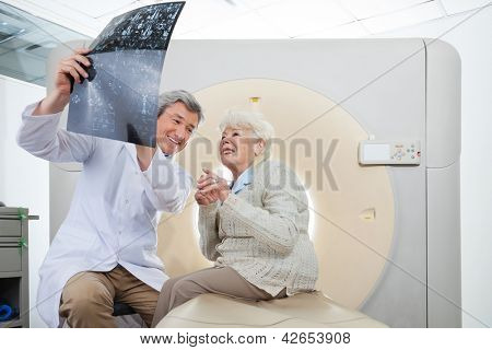 Mature male radiologist with an elderly female patient looking at CT scan results