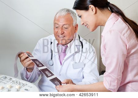 Senior male doctor and female patient looking at ultrasound print