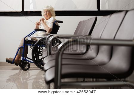 Portrait of a senior woman on wheelchair in hospital lobby