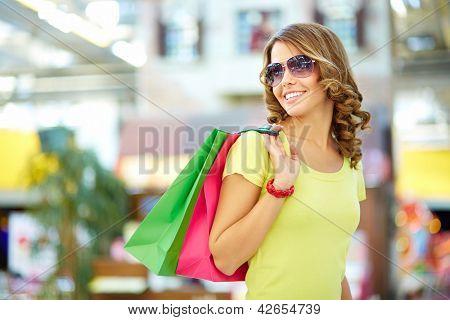 Cool shopping girl enjoying a carefree weekend at mall