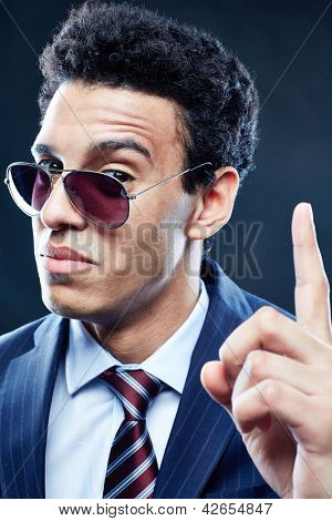 Portrait of calm man in sunglasses pointing upwards and looking at camera