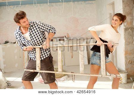 Jovem casal puxando a escada para direções opostas na casa em construção, se divertindo.