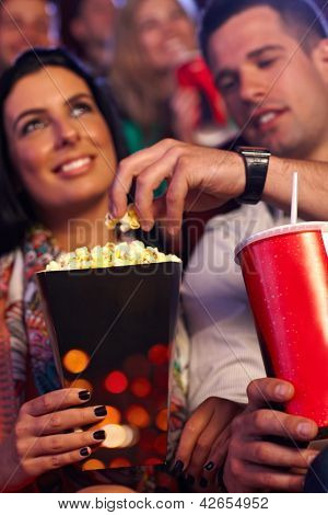 Young couple in multiplex movie theater, eating popcorn. Focus on hands and popcorn.