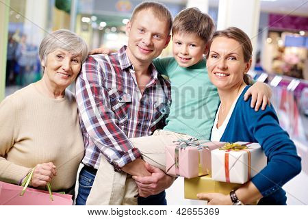 Portrait of happy family looking at camera after shopping