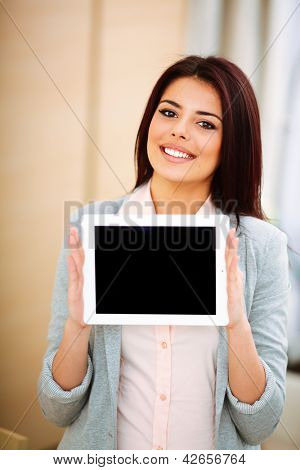 Young beautiful businesswoman showing touchpad where you can put your image or text