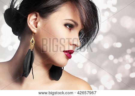 Portrait of beautiful woman with perfect make up over party lights