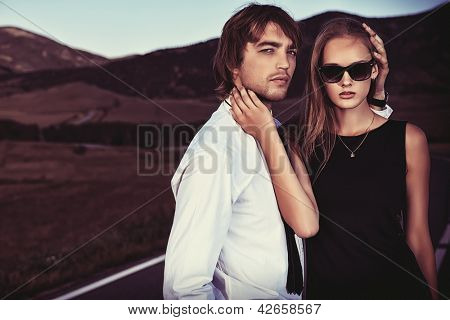 Passionate couple of young people posing on a road over picturesque landscape.