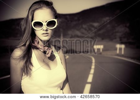 Black-and-white portrait of a beautiful young woman posing on a road over picturesque landscape.