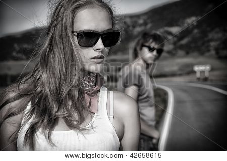 Couple of modern young people posing on a road over picturesque landscape.