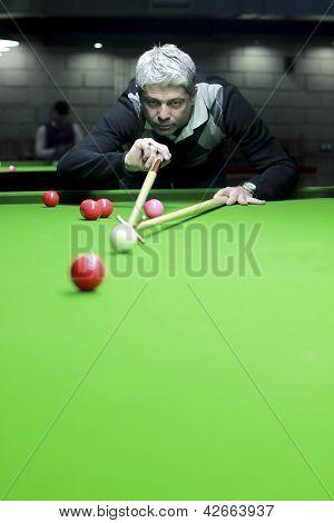 Snooker player hitting ball