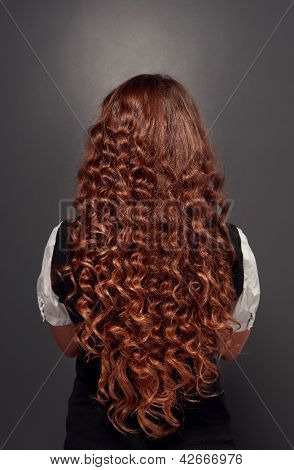 back view of beautiful natural brunette with long curly hair. studio shot over dark background
