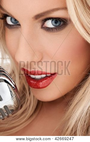 Closeup cropped headshot of a glamorous beautiful blonde vocalist or diva with shiny red lipstick singing at the microphone