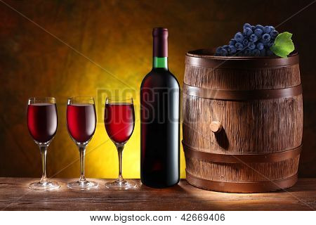 Bottle and a glass of wine with a wooden barrel on dark yellow background with a gradient.