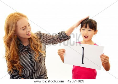 Happy girl studying in English with teacher