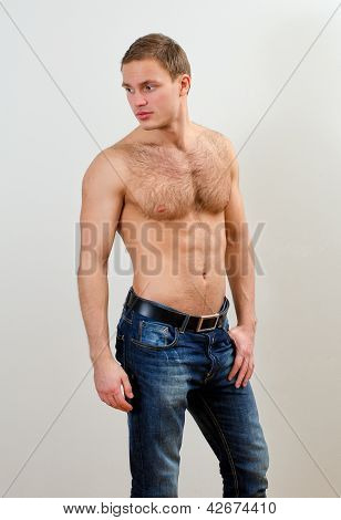 Rapaz bonito em Jeans com Torso nu contra a parede