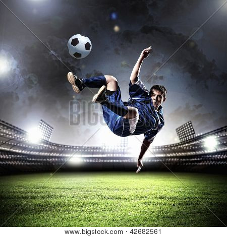 football player in blue shirt striking the ball aloft at the stadium