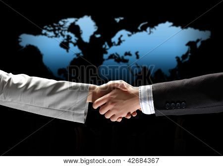 business handshake against black background with map image