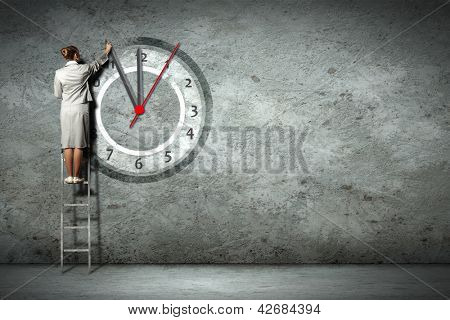 Businesswoman standing on ladder moving hands of clock
