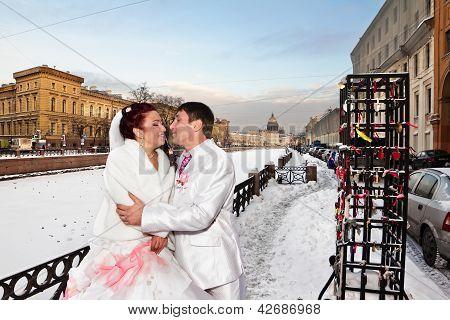 Newlyweds In Wedding Attire Cuddling The Winter Backdrop Of St. Petersburg