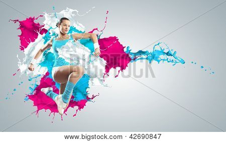 Image of sport girl in jump against color splashes background