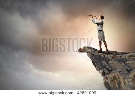 Imagen de empresaria en pie telescopio en la cima de la roca