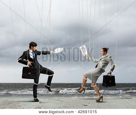Image of businesspeople hanging on strings like marionettes against sea background. Conceptual photography