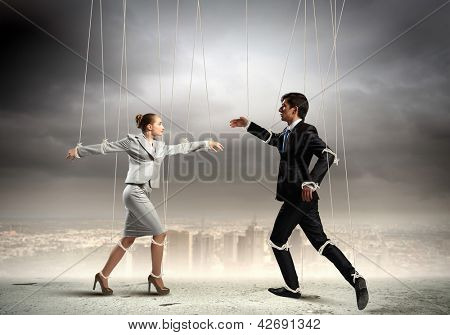 Image of businesspeople hanging on strings like marionettes against city background. Conceptual photography