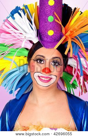 Funny girl clown with a big colorful wig isolated on orange background