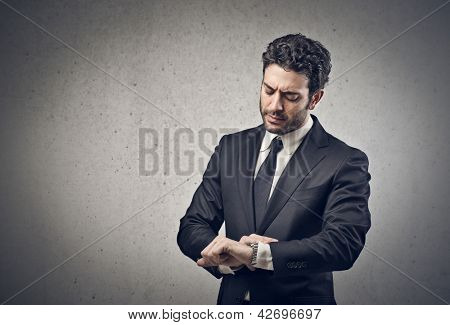 young businessman looking his watch