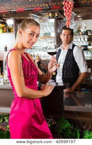 Woman holding a glass of red wine in hand at the bar of hotel or restaurant and smiling