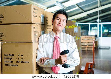 Junger Mann in einem Anzug mit einem Barcode-Scanner in einem Lagerhaus