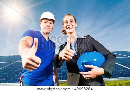 Photovoltaic system with solar panels for the production of renewable energy through solar energy, a technician or worker and the investor or owner standing in front