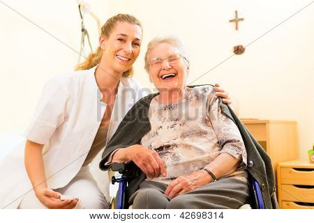 Young nurse and female senior in nursing home, the old lady sitting in a wheel chair