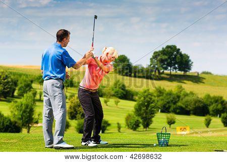 Junge weibliche Golfer auf der Driving-Range mit einem Golf-Pro, übt sie vermutlich