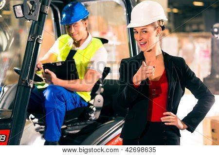 Forklift driver with clipboard at warehouse of freight forwarding company, female super visor or dispatcher pointing to the viewer