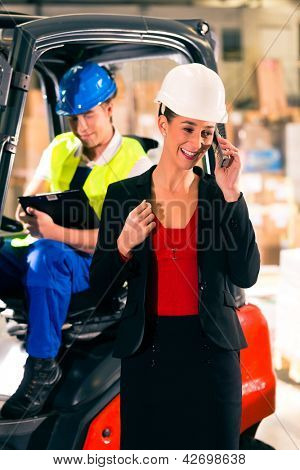 Forklift driver with clipboard at warehouse of freight forwarding company, female super visor or dispatcher with telephone