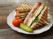 picture of tomato sandwich  - Photo of a club sandwich made with turkey bacon ham tomato cheese lettuce and garnished with a pickle and two cherry tomatoes.