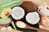 Coconut spa products with body moisturiser, green bath salts, exfoliating scrub, towels and sea shel