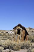 stock photo of outhouse  - A dilapidated outhouse on the verge of collapse - JPG