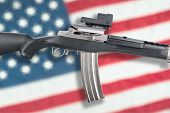 pic of inference  - Am assault rifle over an American flag for use as any gun control inference - JPG