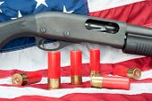 stock photo of ammo  - A pump action shotgun with several shells of ammo resting on an American flag - JPG