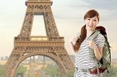 Happy smiling Asian woman travel and look at you in front of famous landmark, Eiffel tower in Paris, France. poster