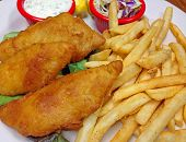 A Plate Of Battered Fried Fish Fillets With French Fries, Tartar Sauce And Cole Slaw