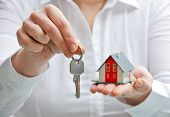 stock photo of possessions  - Real estate agent with house model and keys - JPG