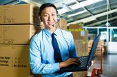 stock photo of warehouse  - Young man in a suit with headset and laptop in a warehouse - JPG